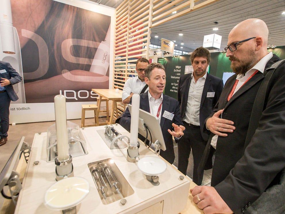 tabak-MARKT Chefredakteur Andreas Ohlberger (r.) lässt sich auf der InterTabac die Vorzüge des Tabakerhitzers IQOS von Philip Morris erklären. (Foto: Ben Horn)